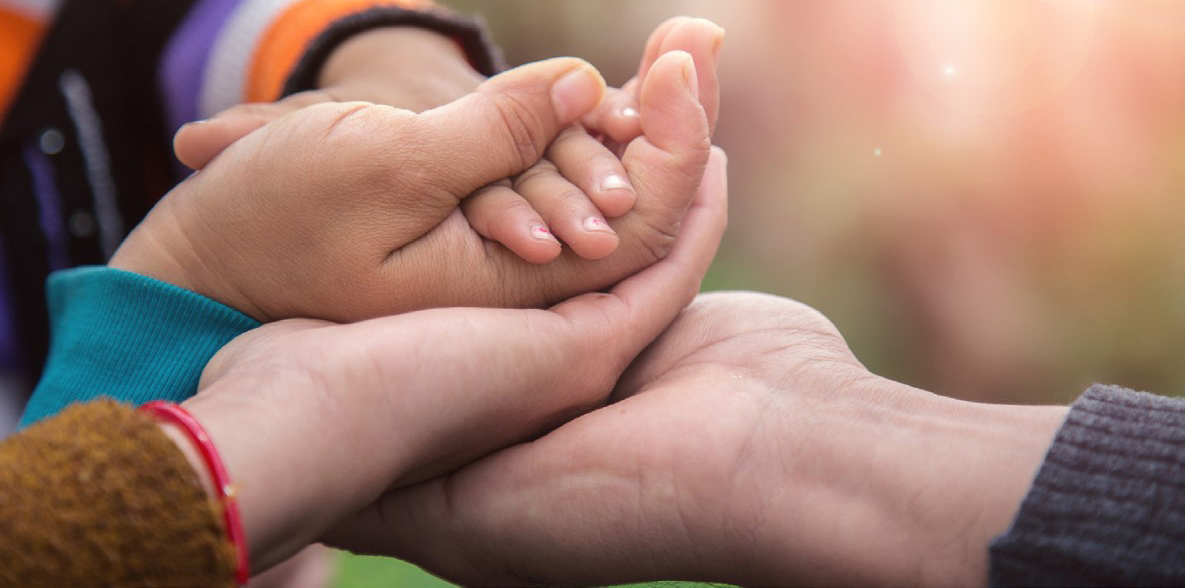 Picture of multiple hands holding a baby's hand