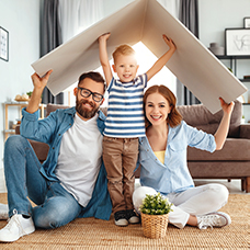 Image of a father, mother, and child under a roof