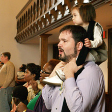 man singing in church with child on shoulders