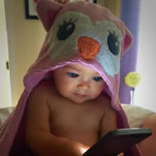 Baby in hooded pink owl snuggy plays with smart phone